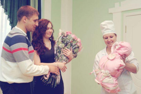 мама с букетом роз и папа смотрят на малыша