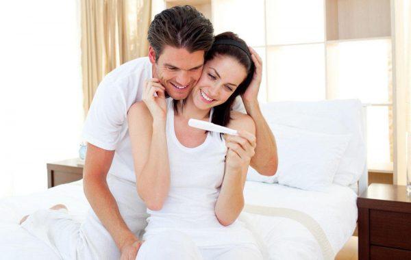 Женщина и мужчина радуются результатам теста на беременность