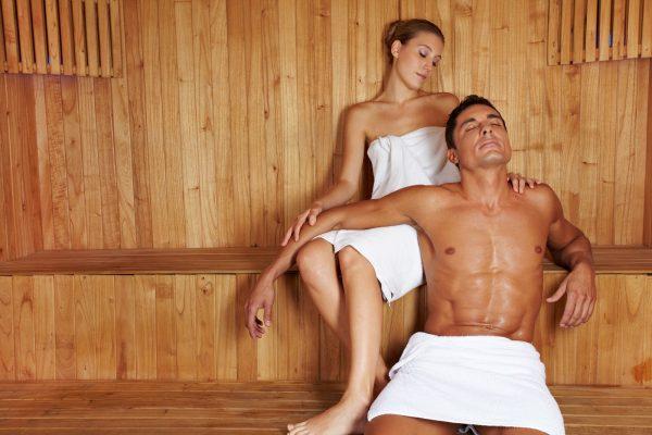 Женщина и мужчина сидят на полках в бане