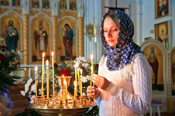женщина ставит свечи в храме