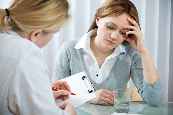Женщина на приёме у врача сидит за столом и одной рукой держится за голову