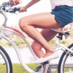 Женщина сидит на велосипеде (фигура видна ниже пояса)