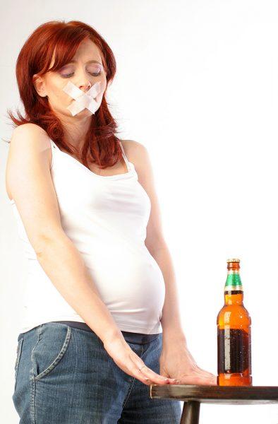 Беременная женщина находится рядом со столом, на котором стоит бутылка пива