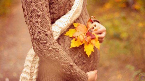 Беременная девушка держит кленовый лист
