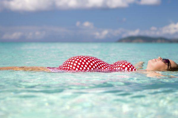 Беременная девушка лежит на воде в море