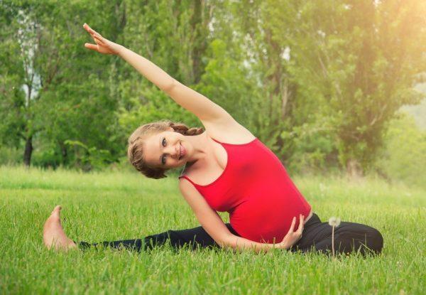 Беременная девушка сидит на траве