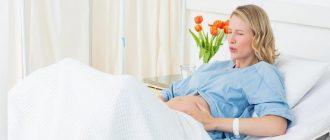 Беременная дышит ртом, сидя на кровати в роддоме