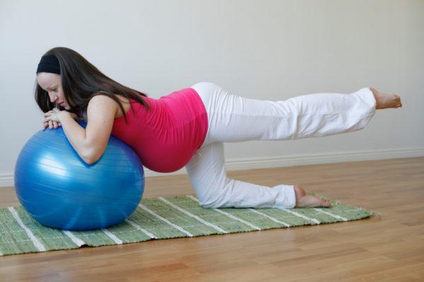 Беременная тренируется на фитболе