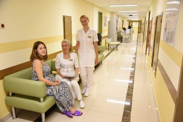беременная сидит на диване с врачами в медицинском центре
