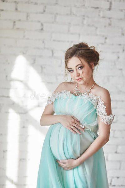 Беременная женщина держит живот руками