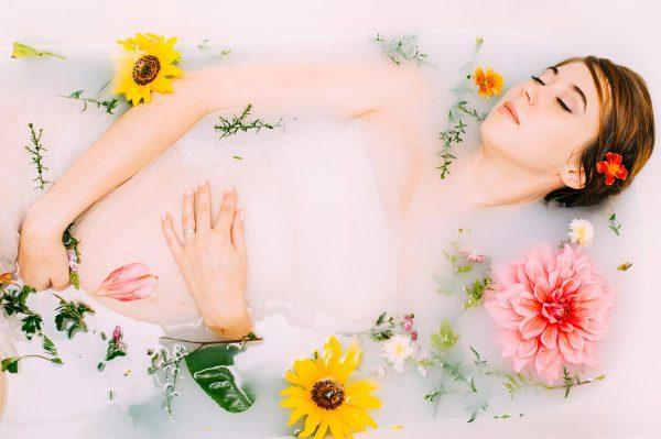 Будущая мама лежит в ванне с цветами