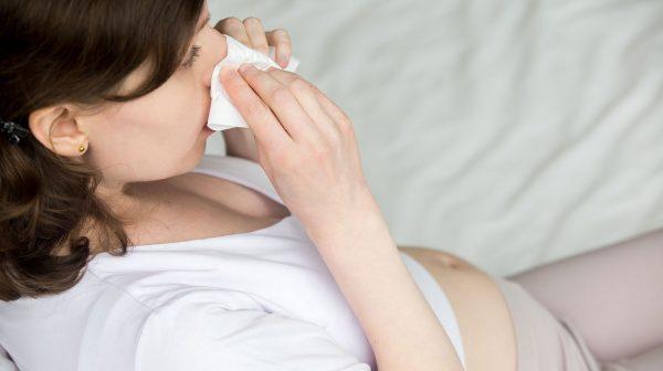 Будущая мама вытирает нос платком