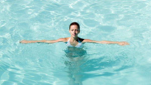 Девушка стоит в бассейне раскинув руки