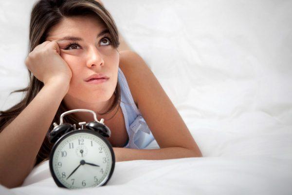 Девушка задумалась возле будильника
