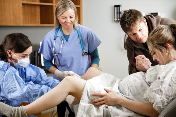 рожающая женщина лежит на кресле в окружении врачей и мужа