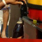 Квас наливают в бутылку из бочки