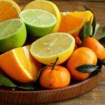 На тарелке мандарины, порезанные лимоны, апельсины и лайм