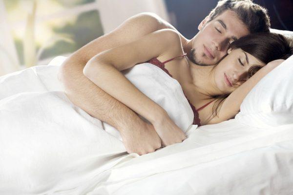 Супруги лежат в постели обнявшись