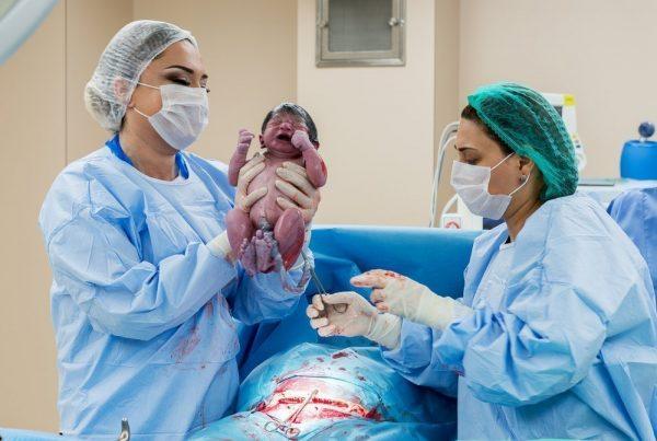 Врачи держат новорождённого ребёнка