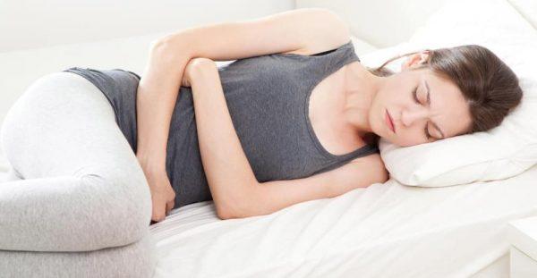 Женщина лежит на кровати и обнимает руками живот