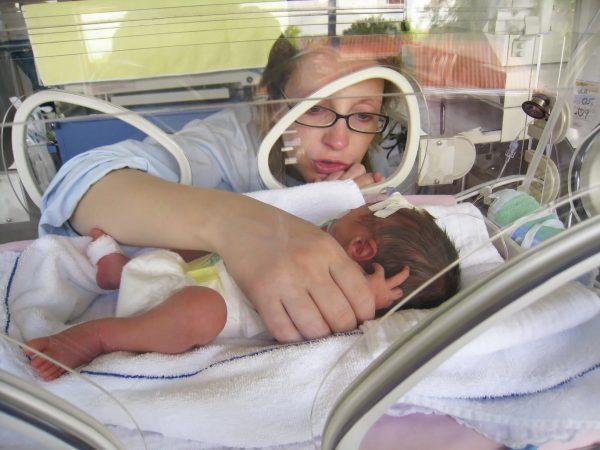 Женщина обнимает младенца в инкубаторе