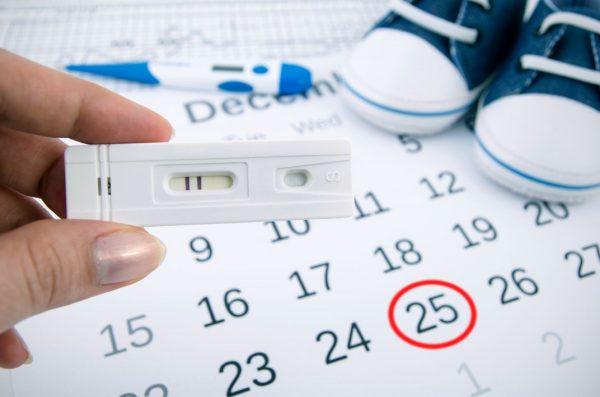 Женская рука с тестом на беременность на фоне календаря