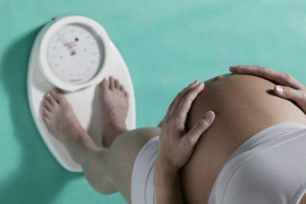 беременная женщина стоит на весах, руки на животе