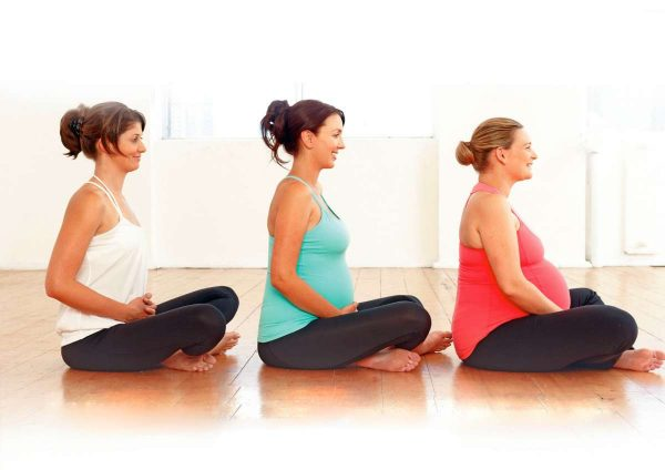 Беременные женщины на разных сроках сидят в ряд