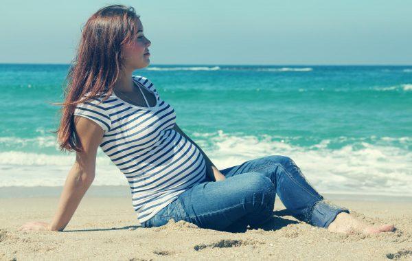 Будущая мама сидит на берегу моря