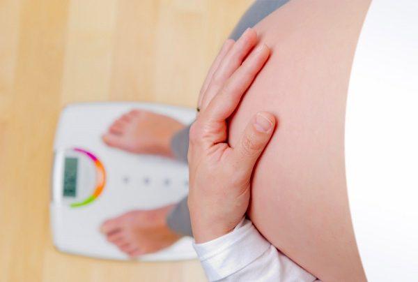 Будущая мама стоит на весах