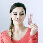 Девушка держит в руке противозачаточные таблетки