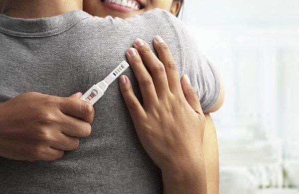 Девушка обнимает мужа и держит тест на беременность