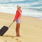 Девушка с дорожной сумкой стоит на берегу моря
