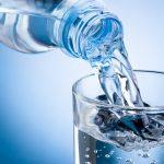 Минеральная вода льётся из бутылки в стакан