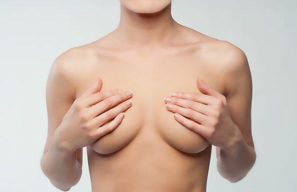 Обнажённая девушка прикрывает груди руками