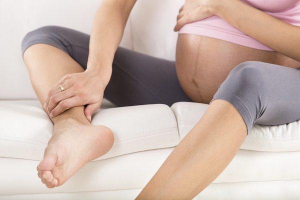Беременная держится за отёкшую ногу
