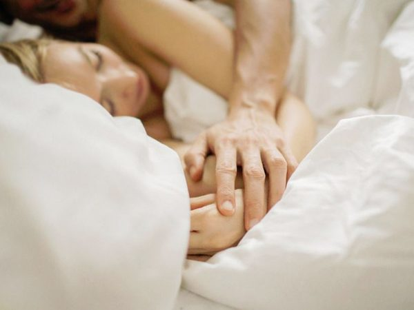 Супруги лежат в кровати и держатся за руки