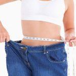 Женщина измеряет себе талию и оттягивает пояс джинсов, которые ей очень велики