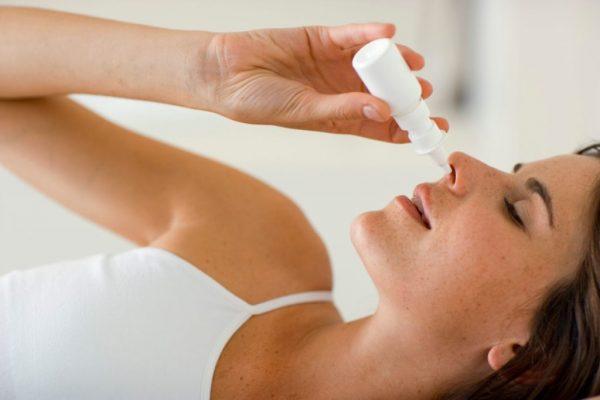 Женщина закапывает нос каплями