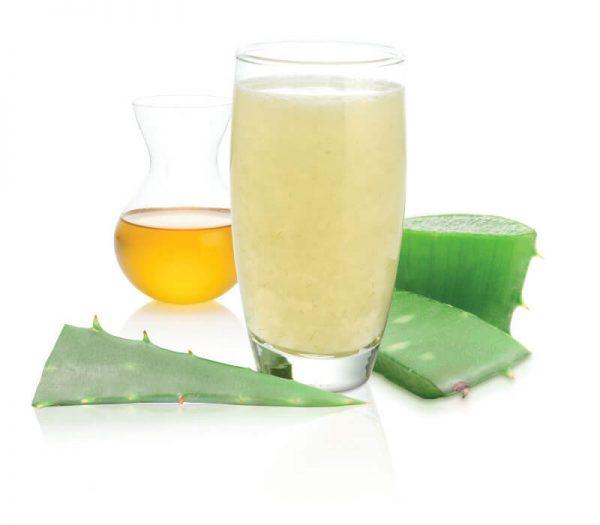 стакан сока алоэ с мёдом, рядом кусочки растения