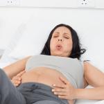 Беременная держится за живот и выполняет дыхательное упражнение