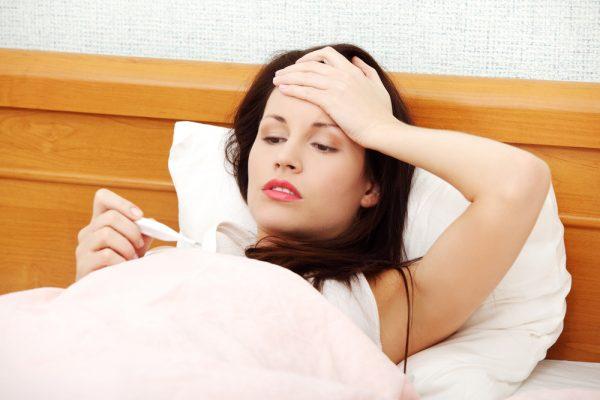женщина в постели смотрит на градусник