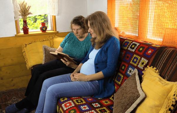 Беременная сидит на диване с бабушкой, бабушка показывает ей книгу