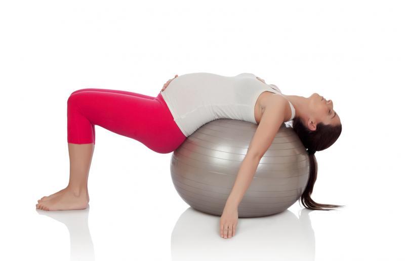 Беременная женщина лежит на фитболе
