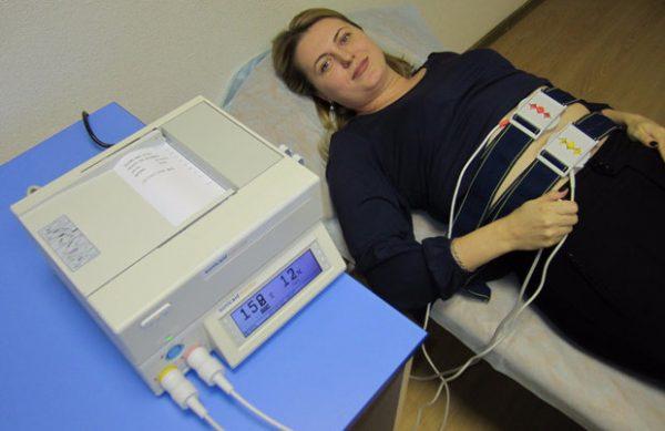 Беременная женщина лежит на кушетке с подключённым аппаратом КТГ