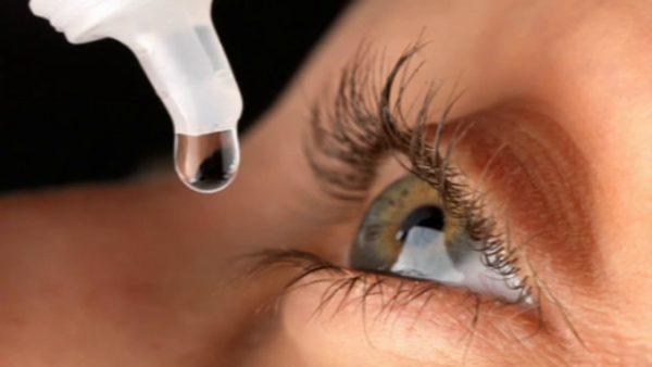 Женщина закапывает в глаз Нафтизин