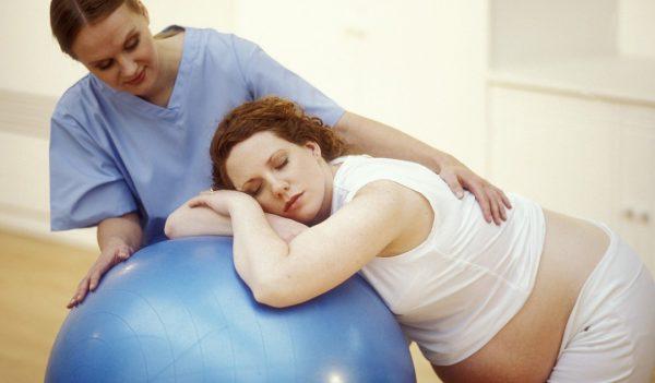 беременная женщина лежит на мяче в сопровождении медика
