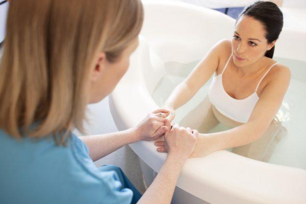 Беременная женщина сидит в ванне и держит за руки другую женщину