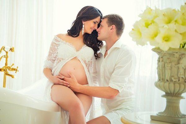 Супруг обнимает беременную жену, она счастливо улыбается