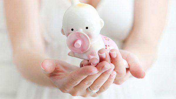 Руки женщины, которые держат фарфорового малыша